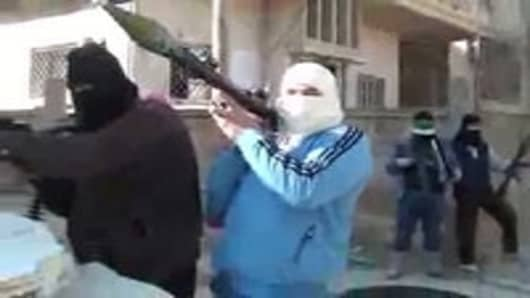 """An image grab taken from a video uploaded on YouTube shows armed men, said to be members of the Free Syrian Army, standing guard in a street in the central town of Rastan in the Homs province."""
